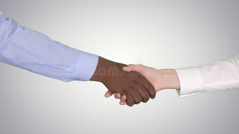 Poignée de main des mains femelles afro-américaines et caucasiennes sur le fond de gradient images stock