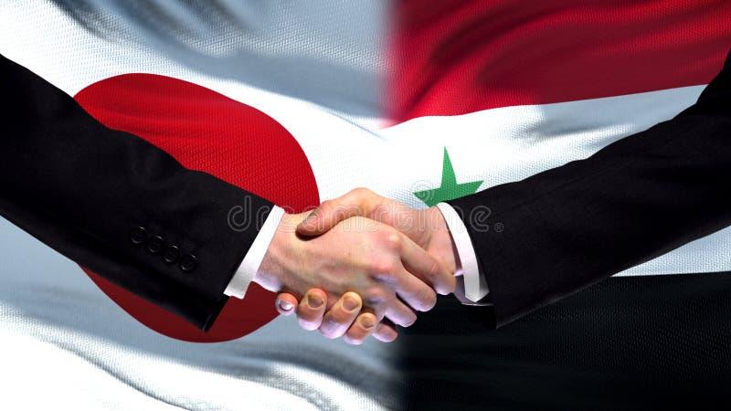 Poignée de main du Japon et de la Syrie, relations internationales d'amitié, fond de drapeau photographie stock