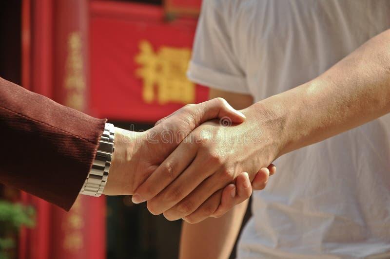 Poignée de main du riche et les pauvrex en l'Asie photos stock