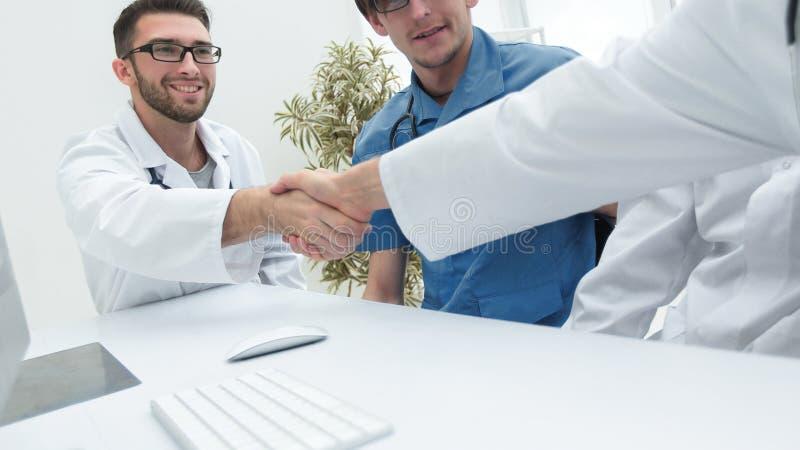 Poignée de main entre les deux médecins au cours de la réunion de fonctionnement images libres de droits