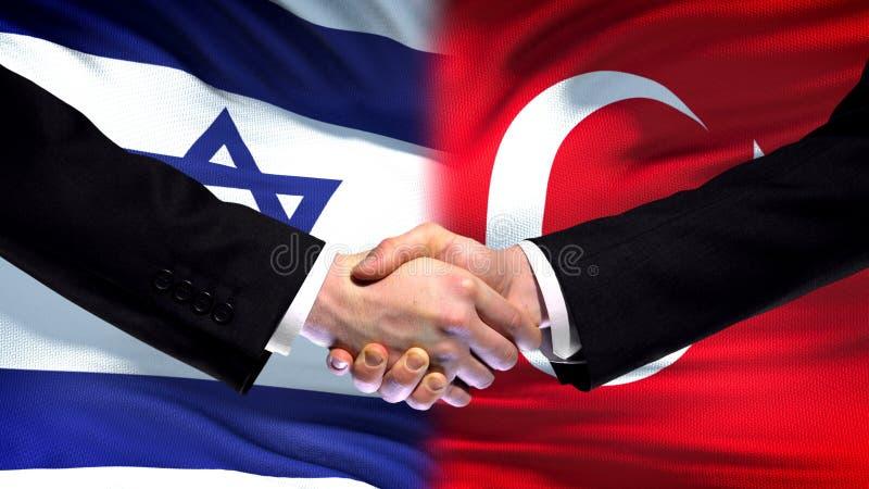 Poignée de main de l'Israël et de la Turquie, relations internationales d'amitié, fond de drapeau image stock