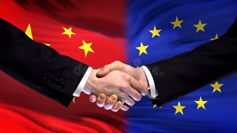 Poignée de main de la Chine et d'Union européenne, amitié internationale, fond de drapeau photographie stock
