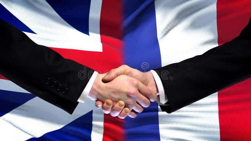 Poignée de main de la Grande-Bretagne et des Frances, amitié internationale, fond de drapeau photos libres de droits