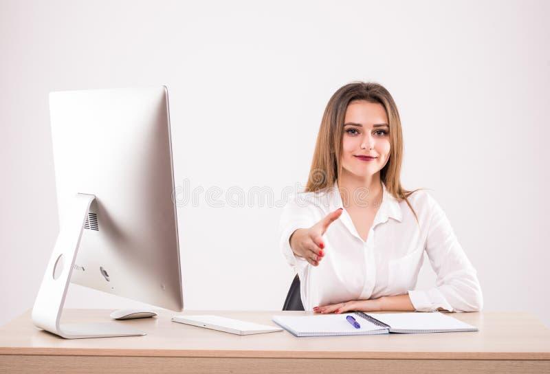 Poignée de main de offre de jeune femme d'affaires gaie attirante sur le fond blanc image libre de droits