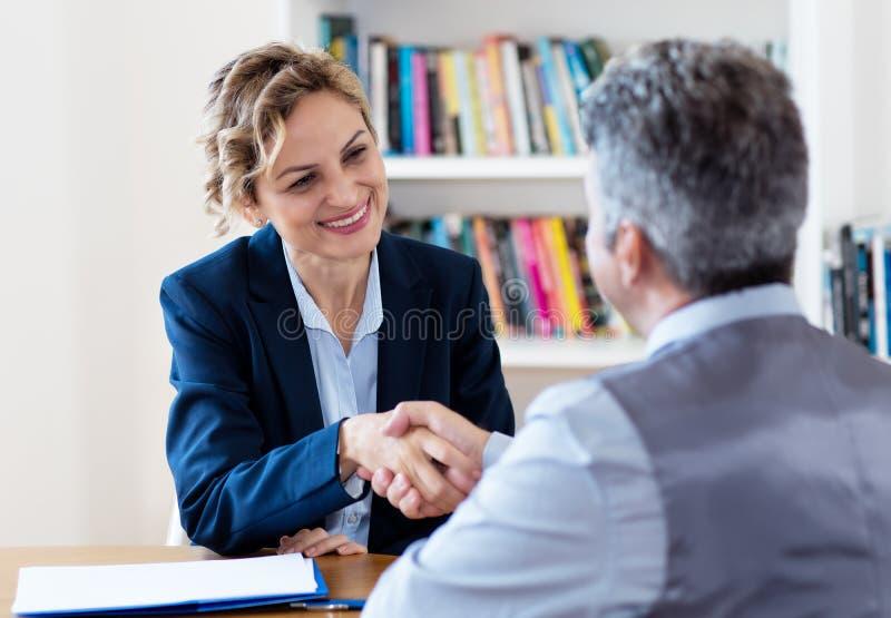 Poignée de main de rire la femme d'affaires mûre après entrevue d'emploi image libre de droits