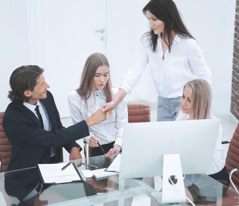 Poignée de main de sourire amicale d'homme d'affaires et de femme d'affaires au-dessus du bureau images stock