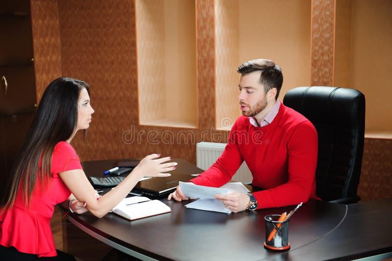 Poignée de main de sourire amicale d'homme d'affaires et de femme d'affaires au-dessus du bureau après entretien agréable image libre de droits