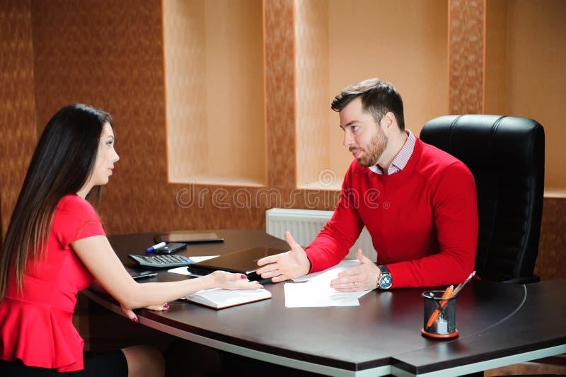Poignée de main de sourire amicale d'homme d'affaires et de femme d'affaires au-dessus du bureau après entretien agréable images libres de droits