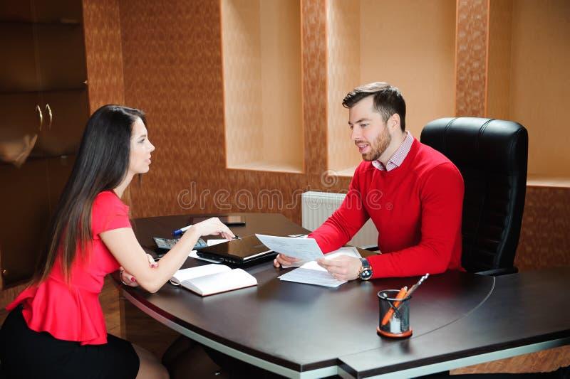 Poignée de main de sourire amicale d'homme d'affaires et de femme d'affaires au-dessus du bureau après entretien agréable, images libres de droits