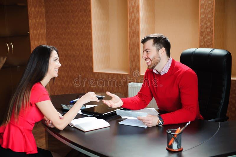 Poignée de main de sourire amicale d'homme d'affaires et de femme d'affaires au-dessus du bureau après entretien agréable image stock