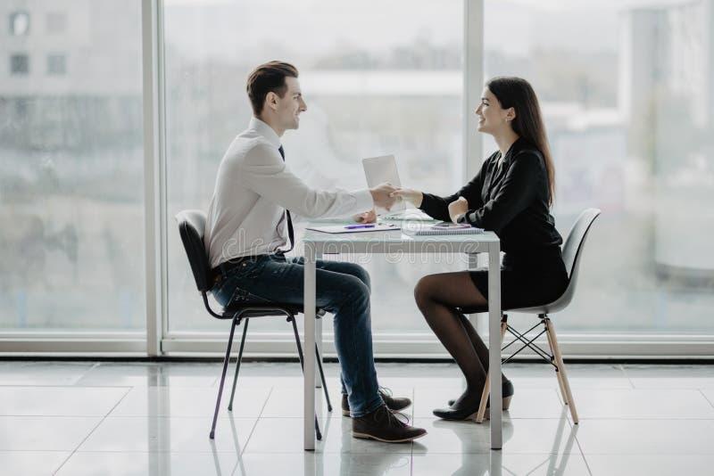 Poignée de main de sourire amicale d'homme d'affaires et de femme d'affaires au-dessus du bureau après entretien agréable et négo photographie stock