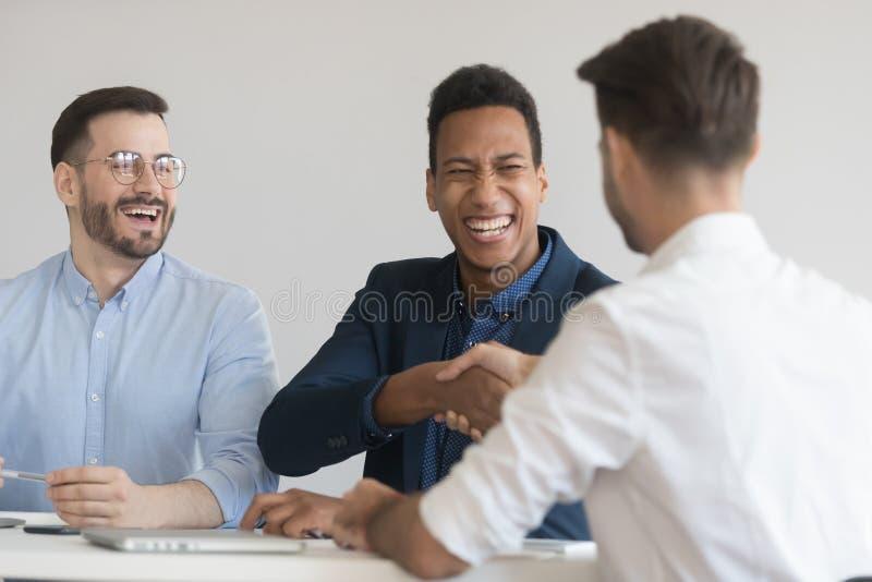 Poign?e de main de sourire d'hommes d'affaires obtenant mise au courant ? se r?unir image libre de droits