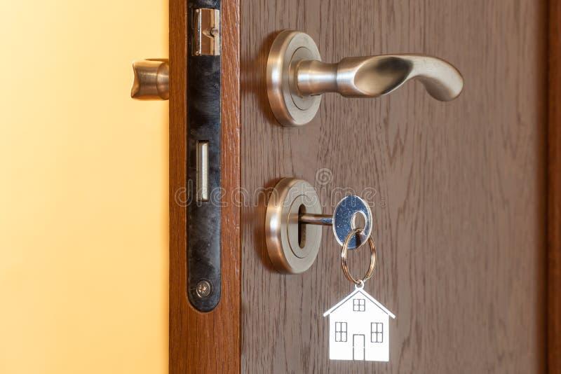 Poignée de porte avec la clé insérée dans l'icône de trou de la serrure et de maison là-dessus image stock