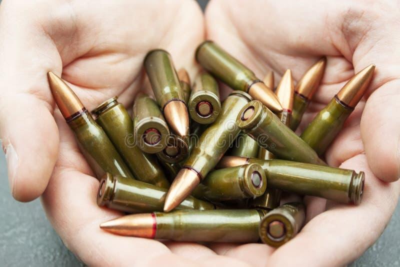 Poignée de 7 verts cartouches de 62 millimètres pour le fusil d'assaut de kalachnikov dans des mains de l'homme images libres de droits