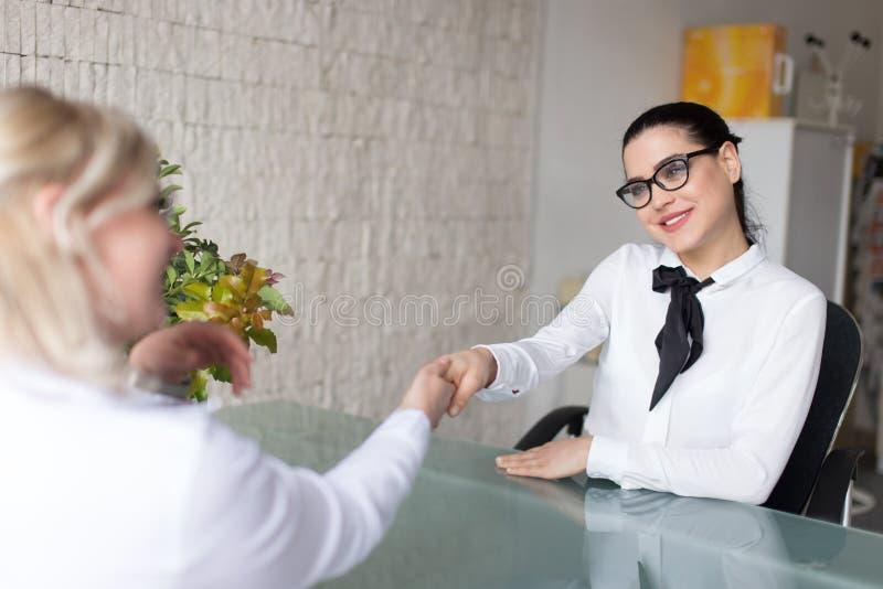 Poign?e de main de femmes d'affaires dans le bureau photographie stock