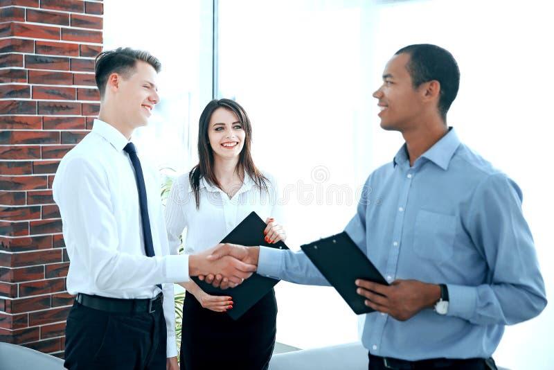Poign?e de main de jeunes associ?s dans le bureau image libre de droits