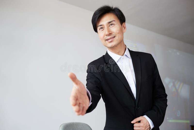 Poign?e de main de offre de jeune homme d'affaires asiatique attirant apr?s affaire d'affaires photos stock