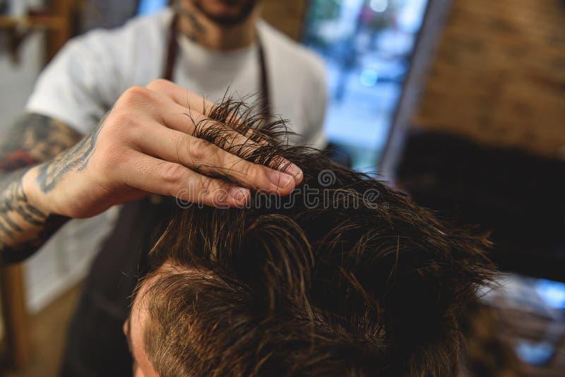 Poils émouvants de styliste en coiffure de client image stock