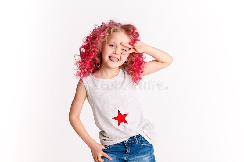 Poils onduleux colorés La petite fille moderne de hippie dans des vêtements de mode, font la paix par sa main photographie stock libre de droits
