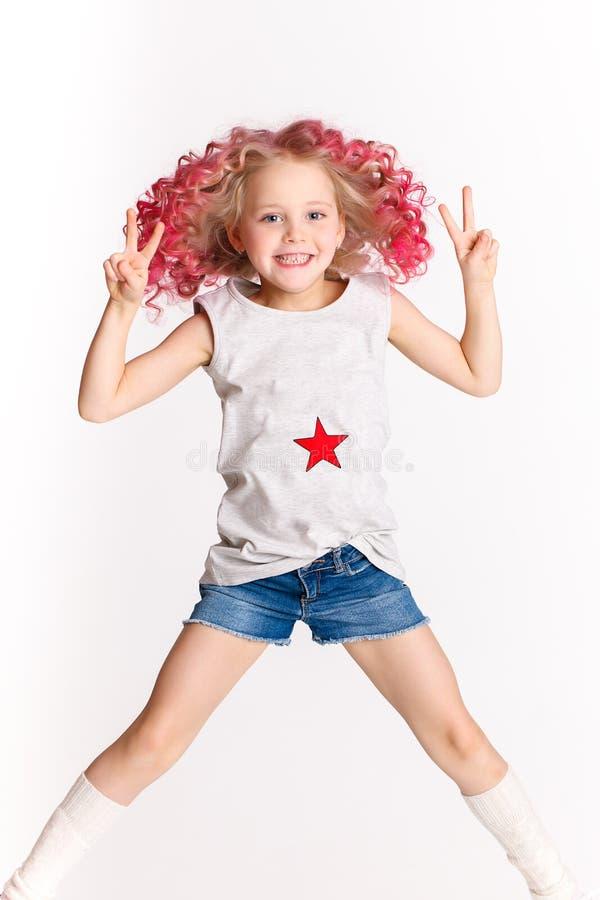 Poils onduleux colorés Petite fille moderne de hippie dans des vêtements de mode, sautant dans le studio et montrant la paix par  photos libres de droits