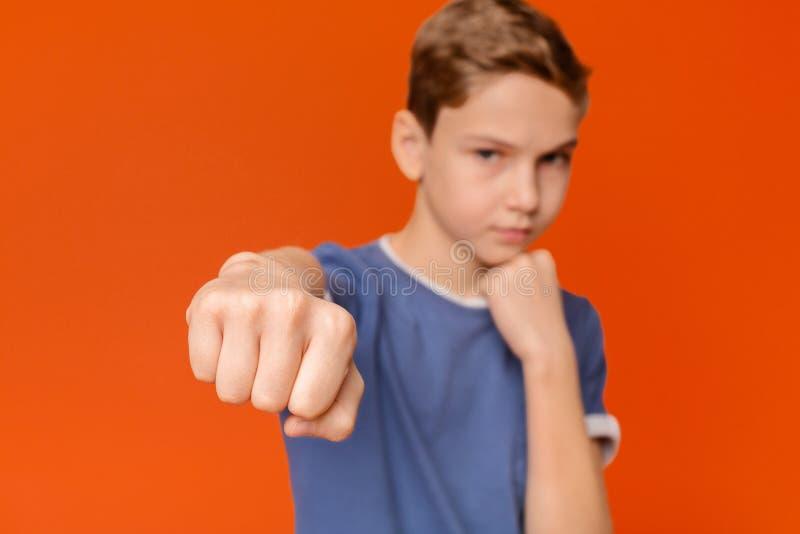 Poinçon de l'adolescence sérieux de boîte de formation de garçon, foyer sur le poing photos libres de droits