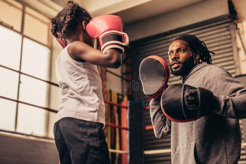 Poinçons de pratique de boxe d'enfant portant des gants de boxe images libres de droits