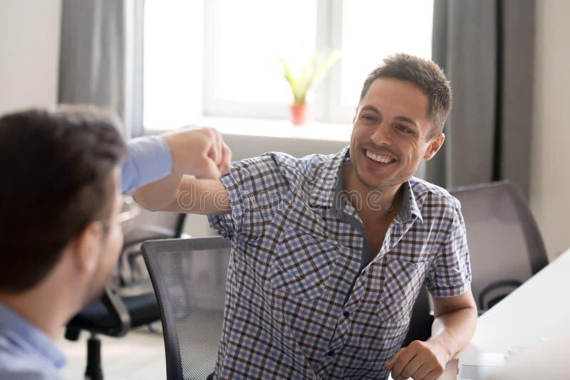 Poing de sourire d'homme se cognant avec le collègue sur le lieu de travail photographie stock libre de droits