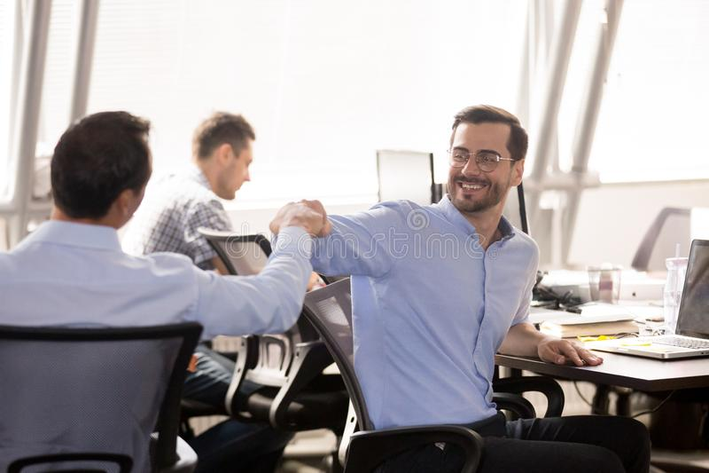 Poing masculin de collègues se cognant sur le lieu de travail, célébrant le succès de travail d'équipe images libres de droits