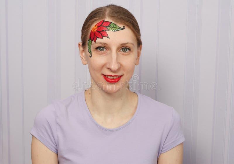 Poinsetia de la flor de la Nochebuena facepainting fotografía de archivo libre de regalías