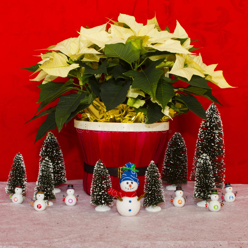 Poinsetia en una cesta roja con el muñeco de nieve y los árboles fotografía de archivo