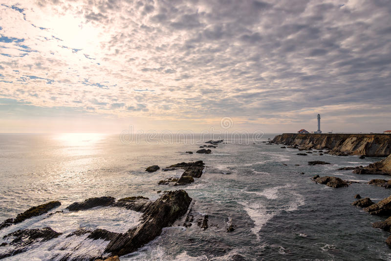 Point Arena Lighthouse with splashing surf at sunset stock photography