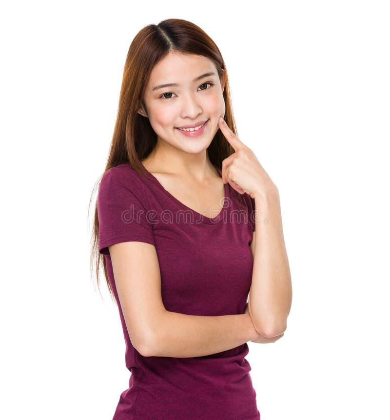 Point asiatique de doigt de femme à ses dents photographie stock