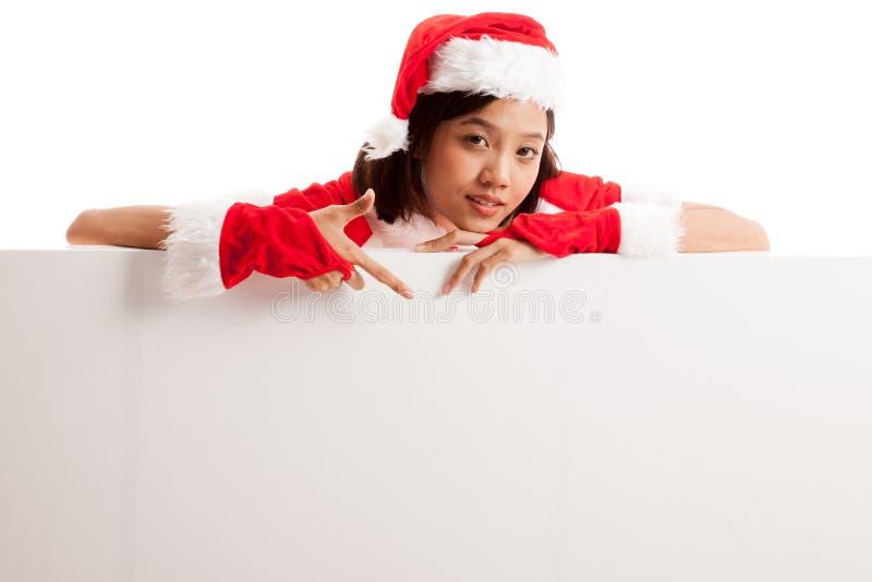 Point asiatique de fille de Santa Claus de Noël vers le bas pour masquer le signe photos stock