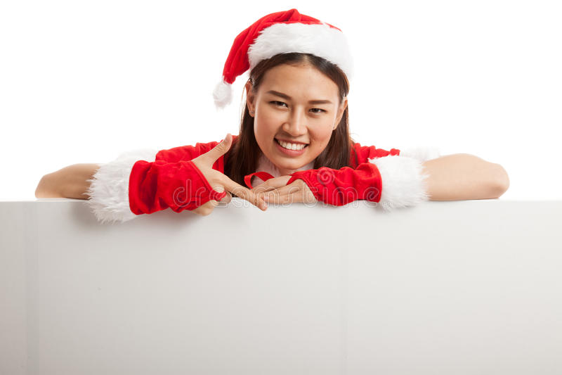 Point asiatique de fille de Santa Claus de Noël vers le bas pour masquer le signe photographie stock