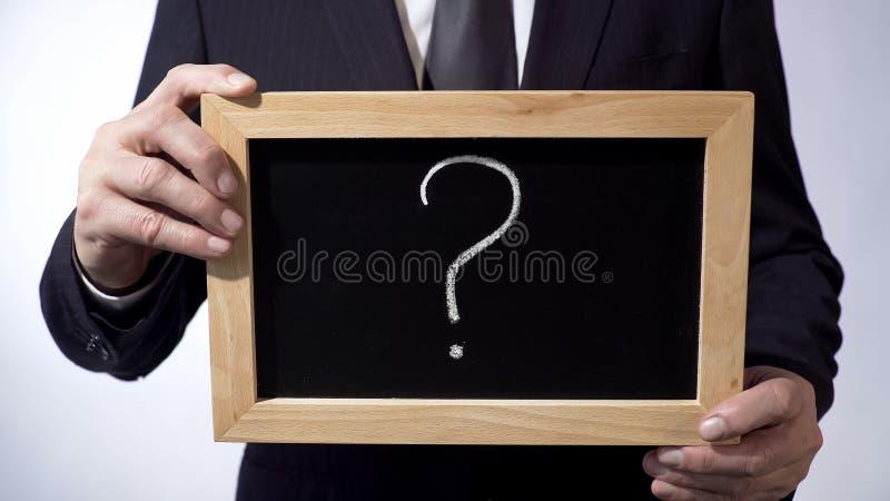 Point d'interrogation écrit sur le tableau noir, homme d'affaires tenant des mains de connexion images libres de droits