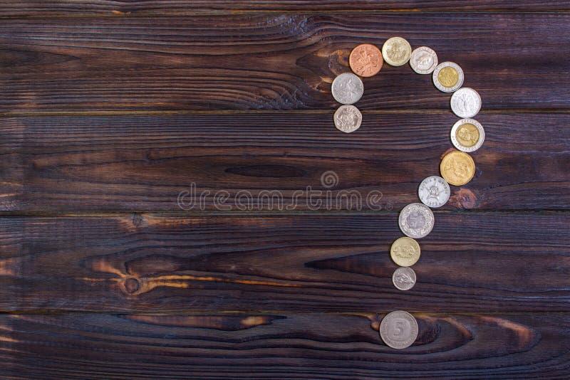 point d'interrogation des pièces de monnaie de différents pays sur un fond en bois photo stock