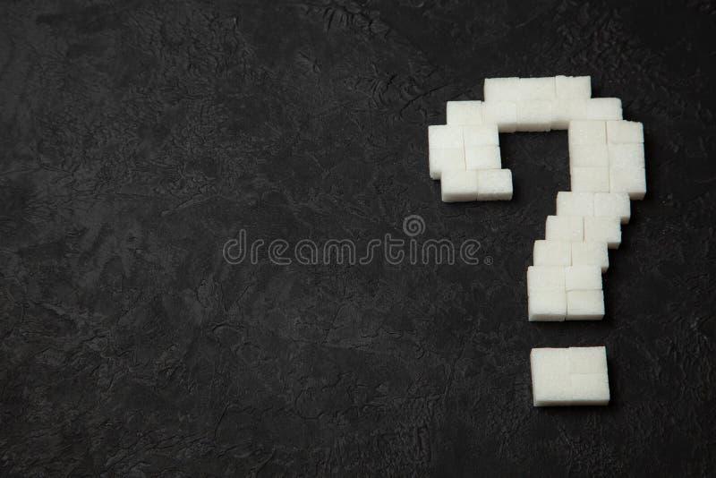 Point d'interrogation fait de cubes en sucre sur le fond noir Comment découvrir si vous avez le diabète ? images stock
