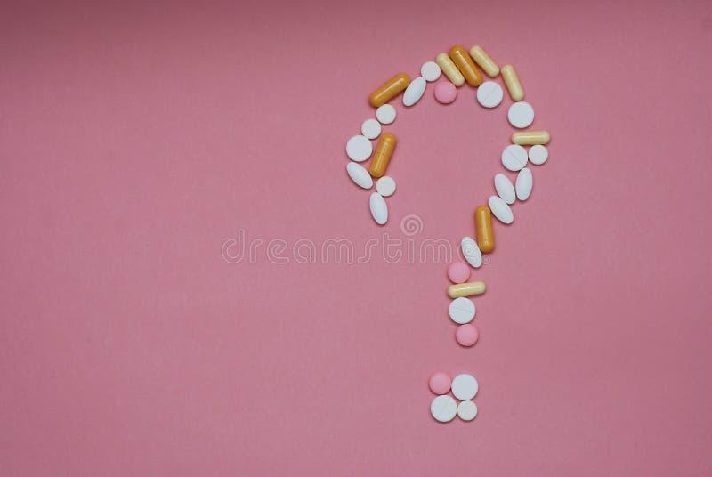 Point d'interrogation fait par des pilules sur le fond rose Médecine créative pour le problème médical de santé, interaction médi photos libres de droits