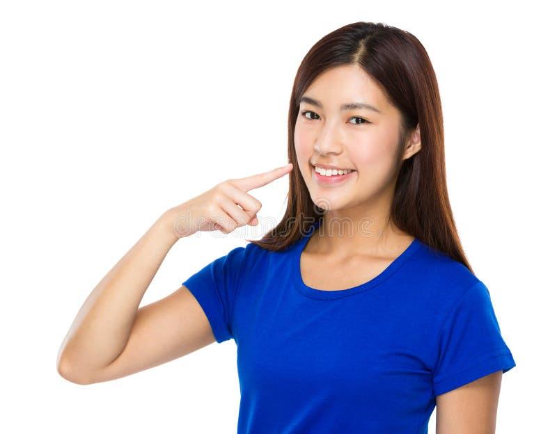Point de doigt de femme à ses dents photographie stock