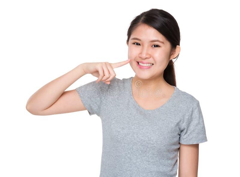 Point de doigt de jeune femme à ses dents images stock