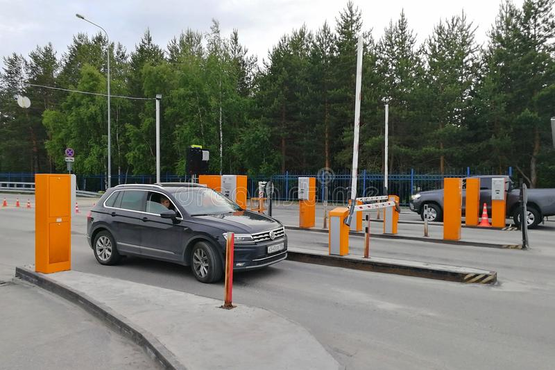 Point of passing cars to airport parking. Auto drives up to slag-boom and payment terminal. Surgut, Russia - June 28, 2019 royalty free stock photo