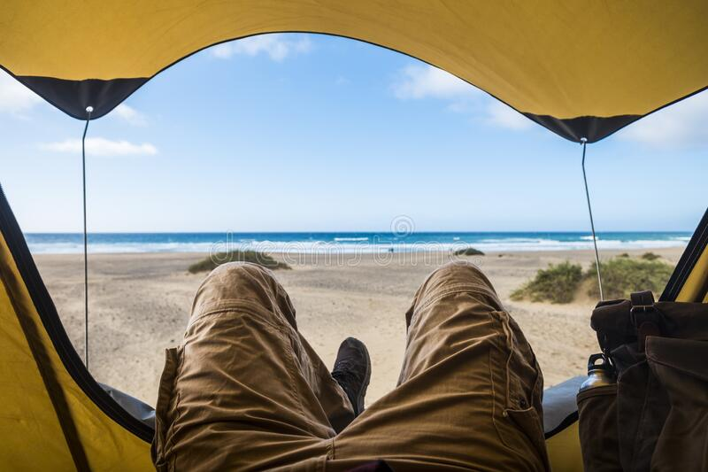 Point of view with laying man inside a tent enjoying relax and adventure in free camping with beach and sea blue sea and sky. Outside - alternative vacation and stock images