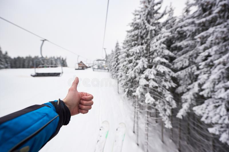 Point of view with thumb up for snowy nature forest around ski lift. Unrecognizable man showing cool to winter landscape royalty free stock photography