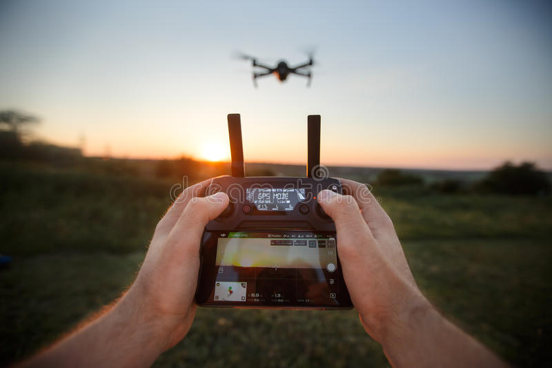 Point of view shot of man holding remote controller with his hands and taking aerial photo video. Quadcopter is flying. Point of view shot of man holding remote stock photography
