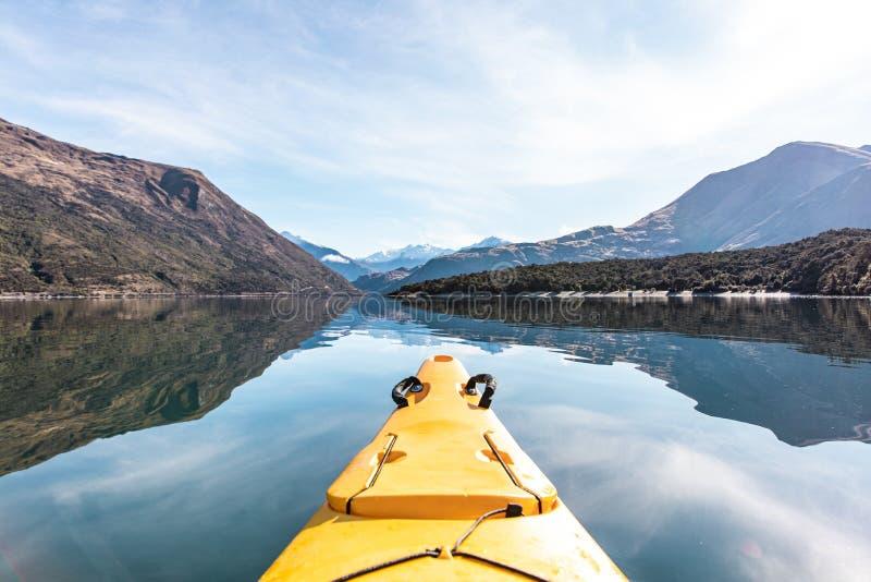 Point of view shot of a yellow kayak boat sailing in beautiful Lake Wanaka, New Zealand royalty free stock image