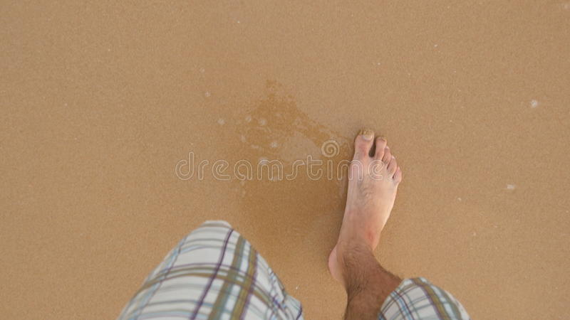 Point of view of young man stepping at the golden sand at sea beach. Male legs walking near ocean. Bare foot of guy royalty free stock photo