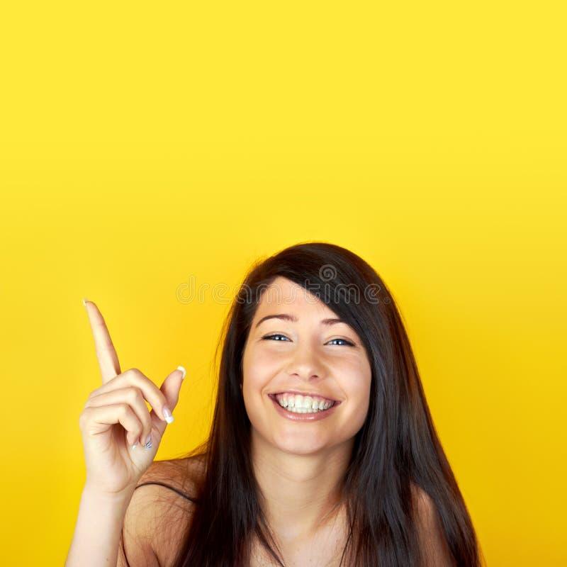 Pointage heureux de jeune femme photo libre de droits