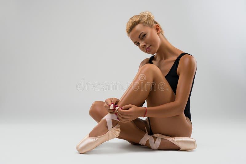 pointe的年轻在地板上的舞蹈家和女用贴身内衣裤 免版税库存图片