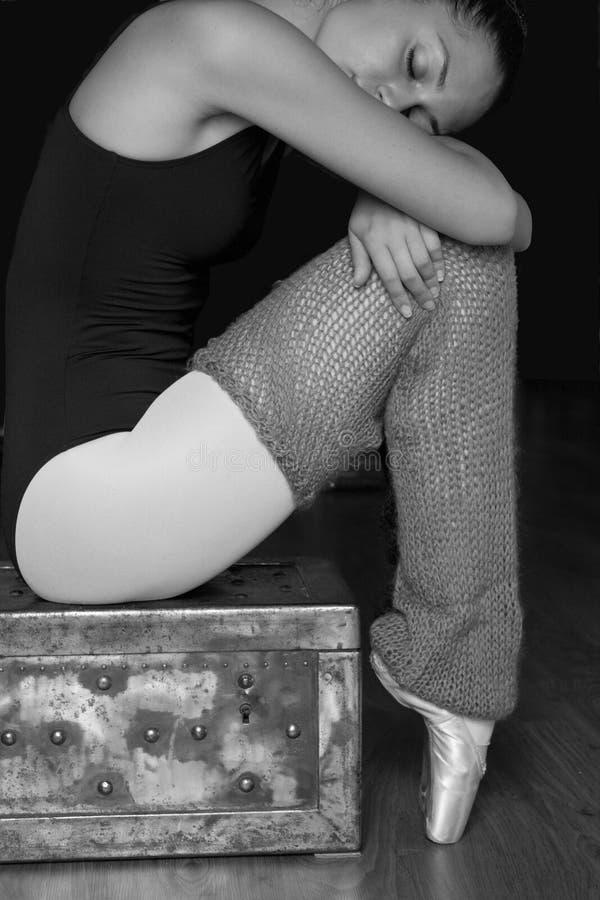 pointe的疲乏的女性舞蹈家穿上鞋子坐条板箱 库存图片