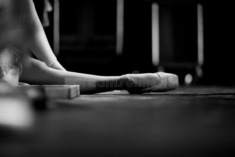 pointe鞋子的芭蕾舞女演员,坐地板 免版税库存图片